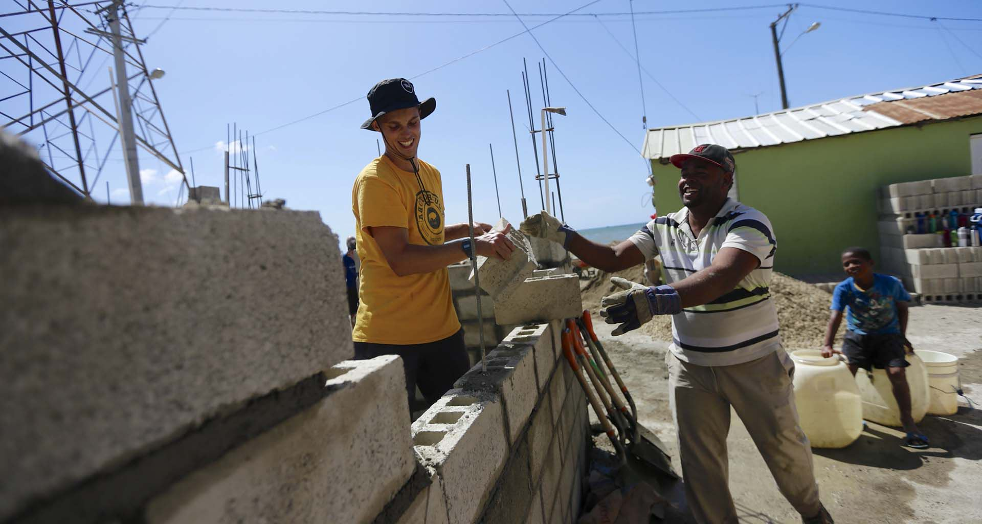 Student helps lay cement bricks to build infrastructure for a rural community in Africa