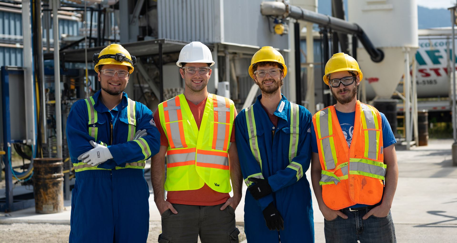 4 students stand at a construction site, wearing safety gear