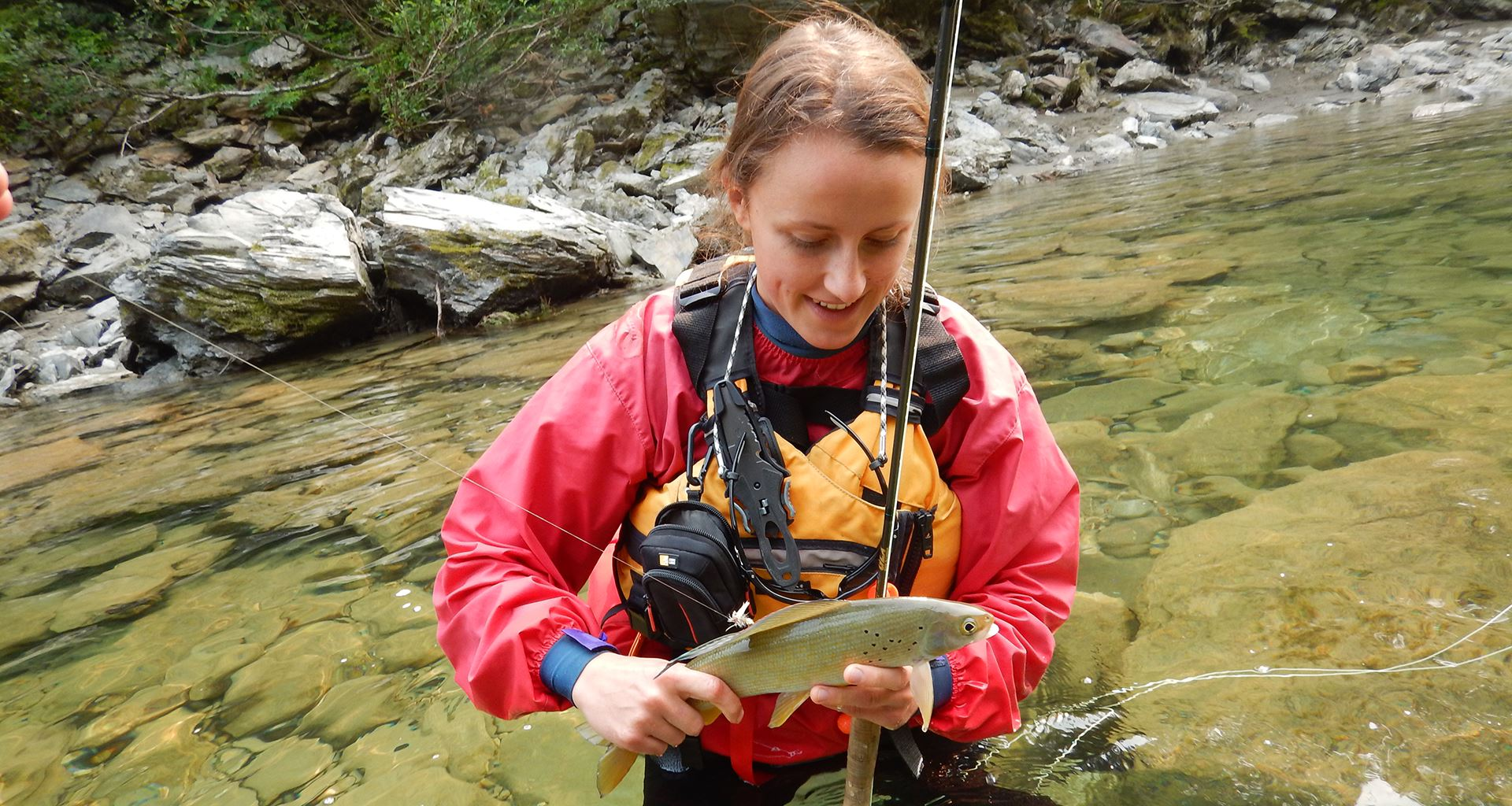 Female co-op student holds a fish while standing in river